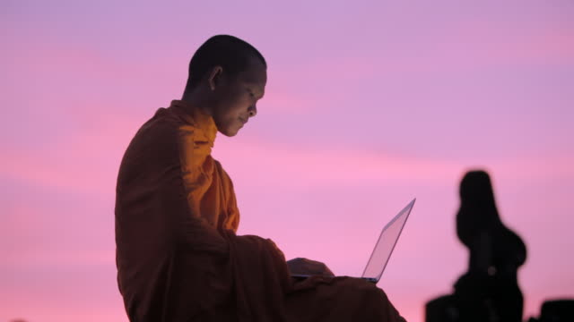 ms a buddhist monk types on a laptop computer on top of an ancient temple at sunrise in angkor wat / siem reap, cambodia - 僧点の映像素材/bロール