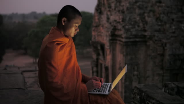 MS A Buddhist monk uses a laptop computer at dawn on an ancient temple at Angkor Wat / Siem Reap, Cambodia