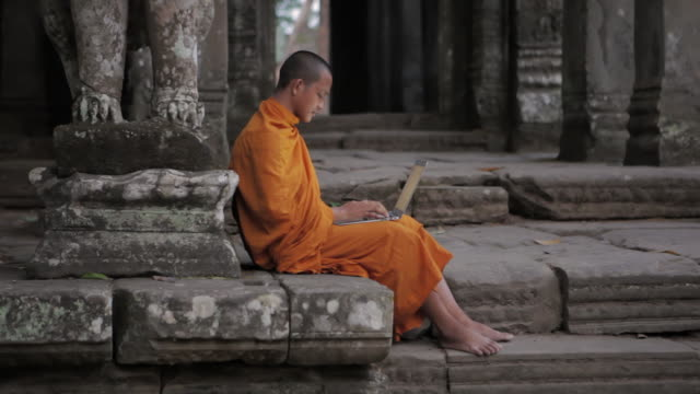 WS, PAN A Buddhist monk uses a laptop computer on the steps of an ancient temple in Angkor Wat / Siem Reap, Cambodia