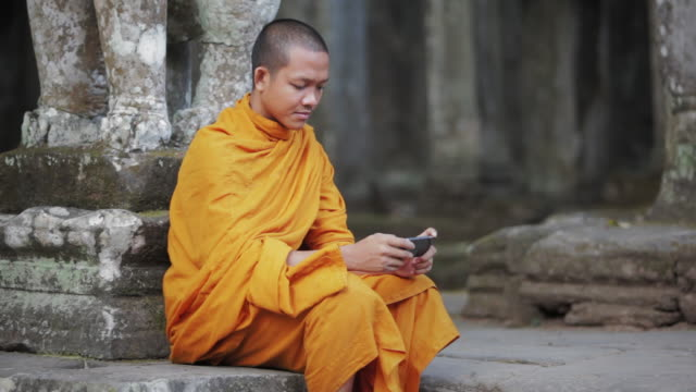 ms a buddhist monk uses a smartphone on the steps of an ancient temple in angkor wat / siem reap, cambodia - contrasts stock videos & royalty-free footage