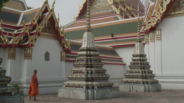 WS PAN buddhist monk walking along pagodas and temples in Wat Pho; enters frame left, exits frame right, RED R3D 4K