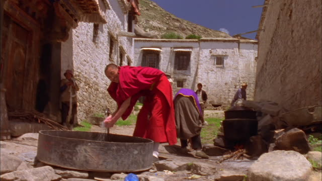 Buddhist monk washes hands under taps Available in HD.