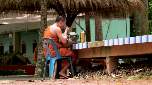 buddhist monk wearing orange robe sitting in chair outdoors eating food - shaved head stock videos & royalty-free footage