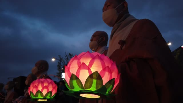 stockvideo's en b-roll-footage met buddhist monks and believers hold colorful lotus lanterns as they pray around a lantern tower in the shape of a buddhist temple pagoda on the... - gelovige