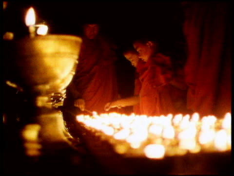 Buddhist monks and boys in orange robes light lots of candles at temple