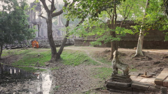 vídeos de stock, filmes e b-roll de ws buddhist monks carrying alms bowls walk past a pond through the lush grounds of an ancient temple in angkor wat on a misty morning / siem reap, cambodia - cambodia