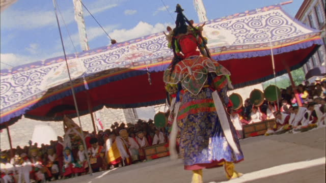 Buddhist monks in elaborate costume dance at parade Available in HD.