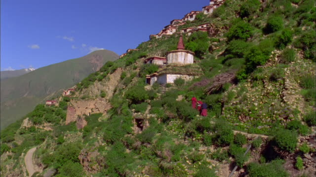 Buddhist monks in robes climb side of mountain, Himalayas Available in HD.