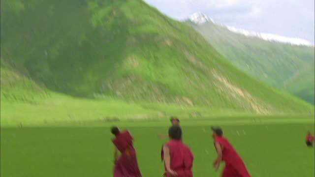 vídeos y material grabado en eventos de stock de buddhist monks in robes play football, tibet available in hd. - hermanos