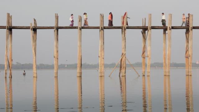 MS, LA Buddhist monks, nuns and local people walk across U Bein Bridge / Mandalay, Myanmar