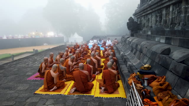 stockvideo's en b-roll-footage met buddhist monks pray at borobudur temple during celebrations for vesak day on may 18, 2019 in magelang, central java, indonesia. - buddhism