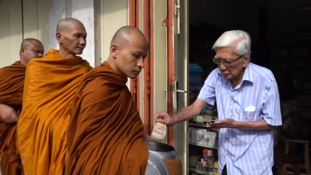 buddhist monks receive religious alms from a buddhist follower as they walk around the streets during pindapata procession on may 10, 2017 in... - buddhism bildbanksvideor och videomaterial från bakom kulisserna