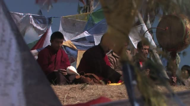 buddhist monks seated among prayer flags, chanting and playing instruments. - conch stock videos & royalty-free footage