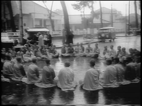 buddhist monks seated in circle in rain on street / south vietnam / newsreel - south vietnam stock videos & royalty-free footage