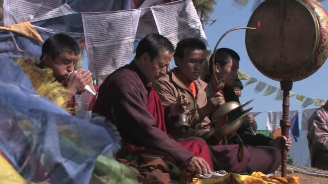 buddhist monks seated in front of prayer flags, playing traditional instruments. - conch stock videos & royalty-free footage