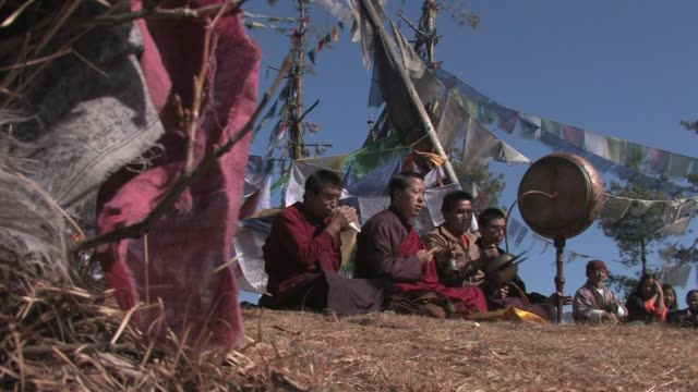 buddhist monks seated in front of prayer flags, playing traditional instruments. - buddhism bildbanksvideor och videomaterial från bakom kulisserna