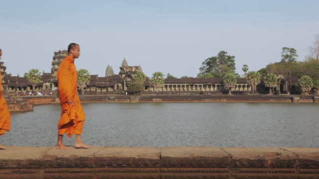 ms buddhist monks walk along the edge of a moat with angkor wat temple in the background / siem reap, cambodia - monk stock videos & royalty-free footage
