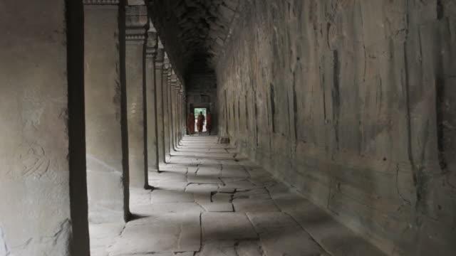 vídeos de stock, filmes e b-roll de ws buddhist monks walk down a pillared corridor in an ancient temple in angkor wat / siem reap, cambodia - cambodia