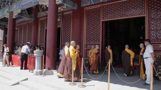 vidéos et rushes de buddhist monks walk into a temple entrance. - fidèle religieux
