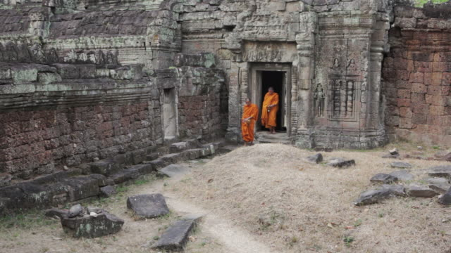 ws buddhist monks walk out of an ancient temple in angkor wat carrying alms bowls to collect offerings / siem reap, cambodia - buddhism stock videos & royalty-free footage