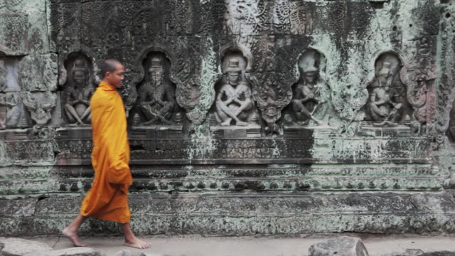 vídeos y material grabado en eventos de stock de ms buddhist monks walk past an intricately carved stone wall in an ancient angkor wat temple / siem reap, cambodia - cambodia
