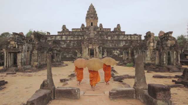 ws buddhist monks walk through the courtyard of an ancient temple in angkor wat carrying parasols / siem reap, cambodia - parasol stock videos & royalty-free footage