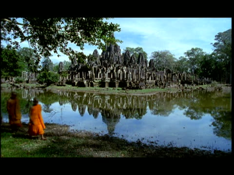 ms, pan, buddhist monks walking along moat, angkor wat temple in background, angkor, cambodia - moat stock videos & royalty-free footage