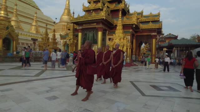 buddhist monks walking in the shwedagon pagoda. yangon, myanmar (burma). - buddhismus stock-videos und b-roll-filmmaterial
