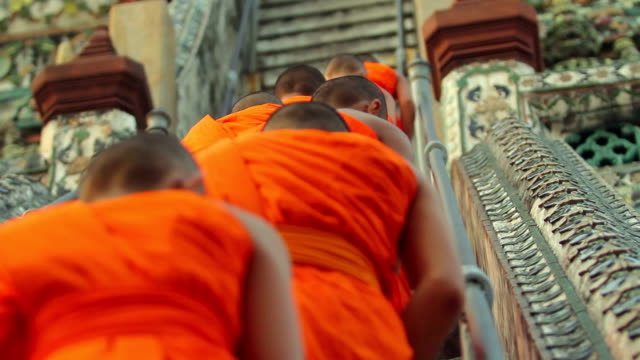 Buddhist monks walking up steep stairs at a temple