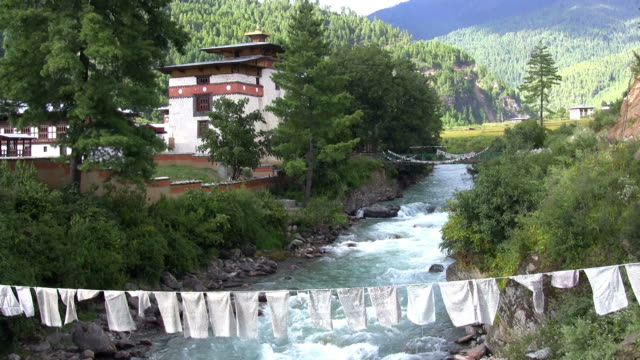 buddhist prayer flags across a river in bhutan - bhutan stock videos & royalty-free footage