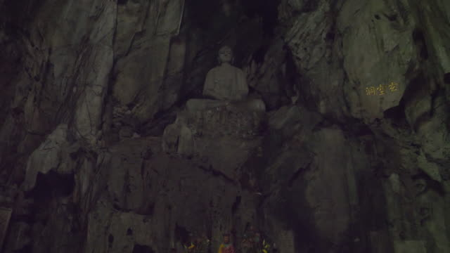 a buddhist shrine inside  a marble cave - stone wall stock videos and b-roll footage