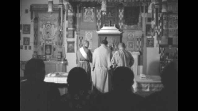 vídeos y material grabado en eventos de stock de buddhist temple in asia probably lama and monks standing in front of shrine backs of heads in silhouette in fg they turn and approach altar / ms lama... - lama