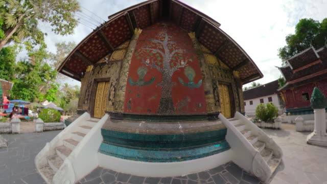 zo / buddhist temple wat xieng thong with a large tree of life mosaic on the sim - 金箔点の映像素材/bロール