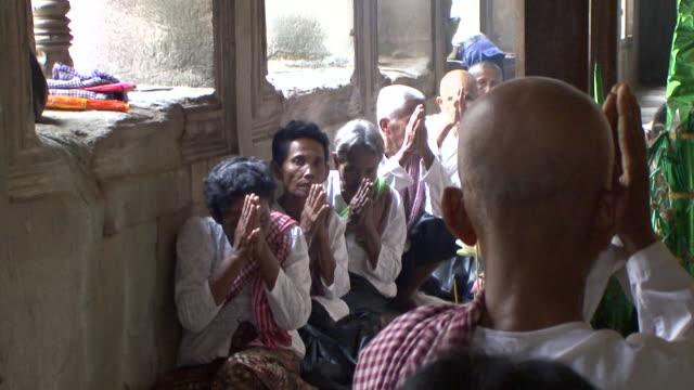 MS Buddhists chanting around statue of Bodhisattva / Siem Reap, Cambodia