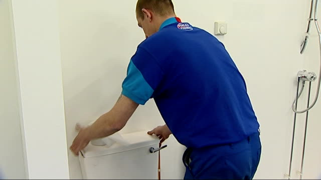 vidéos et rushes de criticism; location unknown: plumber repairing toilet cistern workman sawing plank of wood - plombier