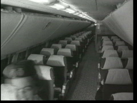 survey criticises bargain flights hidden costs; lib ???: int aircraft b/w air hostess along aisle of empty aircraft cabin b/w cabin crew in galley of... - b rolle stock-videos und b-roll-filmmaterial