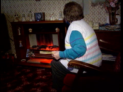 vídeos de stock, filmes e b-roll de old woman sitting next electric fire in lounge and doing crosswords in book - old book
