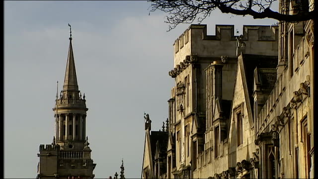 reaction general views of oxford england oxfordshire oxford ext university building seen through archway / spires seen through trees / ornate... - oxford university stock videos & royalty-free footage