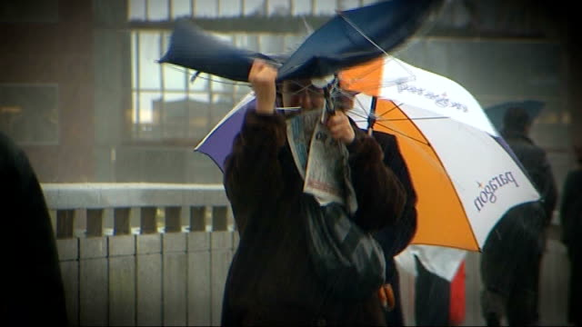 Budget review EXT City commuters along in heavy rain storm some struggling with umbrellas