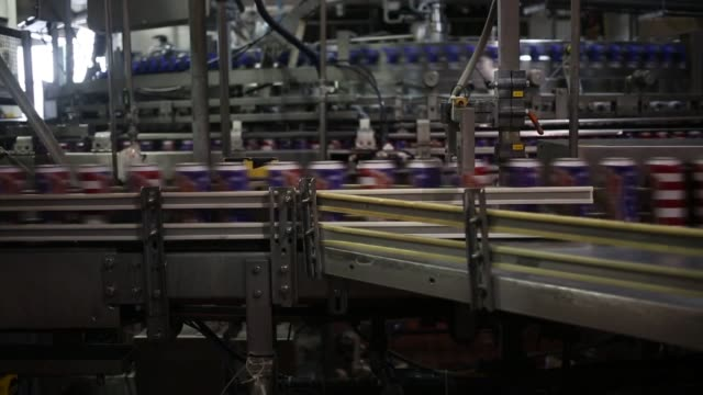 Budweiser beer is made at the Anheuser Busch Budweiser Brewery in St Louis Missouri US Budweiser beer cans with the red white and blue design speed...