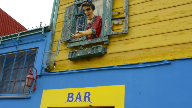Buenos Aires Argentina La Boca colorful street with murals out window of bar of building