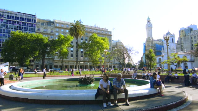 Buenos Aires Argentina Plaza de Mayo people sitting on fountain in main square of city center