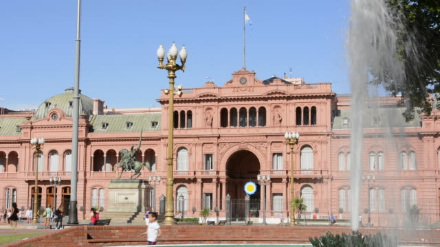 buenos aires argentina plaza de mayo with pink house casa rosada in square in city center with argentine flag and fountain - casa rosada stock-videos und b-roll-filmmaterial