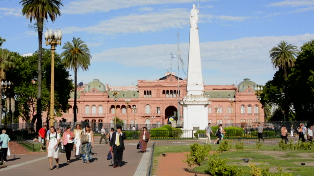 buenos aires argentina plaza de mayo with pink house casa rosada in square in city center with argentine flag  and people walking - casa rosada stock-videos und b-roll-filmmaterial