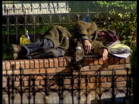 crisis lib buenos aires tgv rooftops of city homeless man laying on bench homeless man hanging cloth on railings homeless man sat on bench young girl - argentina stock videos & royalty-free footage
