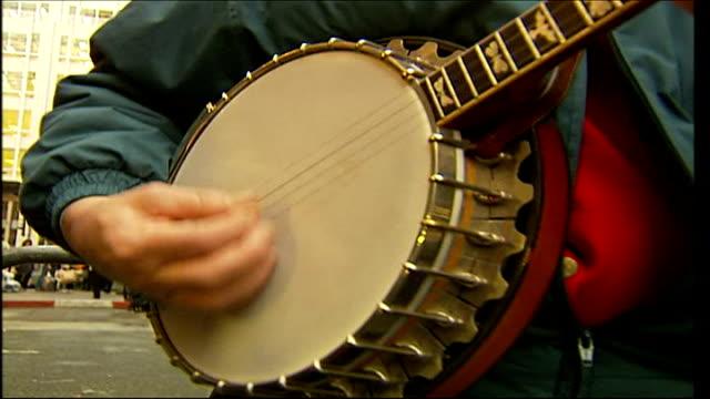 'buffy the vampire slayer' opens harrods sale england london knighstbridge ext man playing banjo - banjo stock-videos und b-roll-filmmaterial