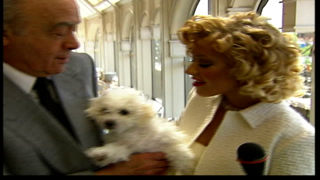 'Buffy the Vampire Slayer' opens Harrods sale T28060422 Christina Aguilera holding dog with Al Fayed as posing for photocall