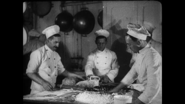 vidéos et rushes de bugler blowing his horn to call passengers to dinner / the head chef working with his cooks, cook using a giant mortar and pestle, prep cook making... - titanic