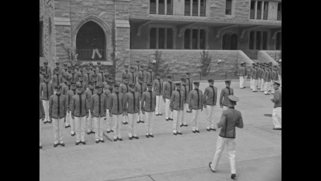 Bugler in front of tent / US Military Academy cadets in uniform with firearms running to position at West Point / they begin marching / cadets...