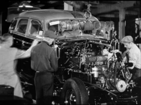 buick sedan assembly line factory workers working on front of car body workers lowering body onto chassis material onto conveyor fender placement ha... - industria dell'automobile video stock e b–roll